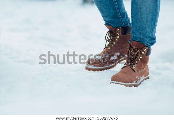 Men's winter boots on snow. Brown men's warm winter boots closeup