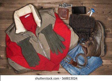 Men's winter clothes laid out on a dark wood floor. Items include, Sweater, Scarf, Gloves, Pants, Boots, belt, Wallet.