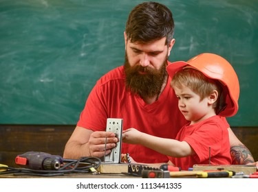 Mens work concept. Father with beard teaching little son to use tools in classroom, chalkboard on background. Boy, child busy in protective helmet makes by hand, repairing, does crafts with dad.