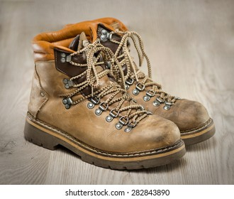 Mens working or hiking boots made of brown leather, vintage look, on wooden background.