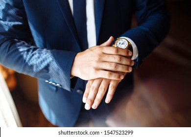 Men's wrist watch, the man is watching the time. Businessman clock, businessman checking time on his wristwatch. Groom's hands in a suit adjusting wristwatch, wedding preparations, groom accessories.