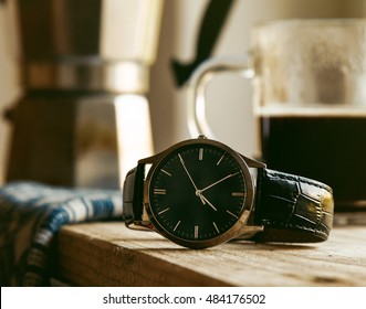 men's wrist watch on wooden table with coffee in morning light