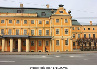 Menshikov palace in Saint Petersburg, Russia. Empty street with one person walking on Universitetskaya embankment. Petrine baroque building architecture and empty street in front