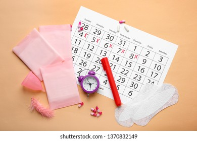 Menstrual calendar with feminine products and alarm clock on color background