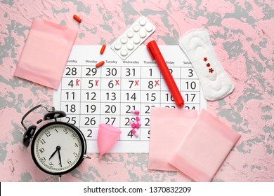 Menstrual calendar with feminine products, pills and alarm clock on color background