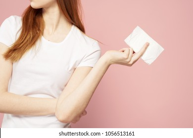 menstrual cycle, hygiene, health care, gasket in the hand on a rosy background