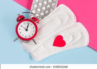 Menstrual pads, alarm clock, hormonal contraceptive pills. Menstruation period concept. Pain reliever for menstrual pain. Menstrual retardation concept