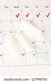 menstruation calendar with cotton tampons, close-up