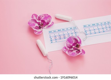 Menstruation. Calendar, tampons, orchid flowers on a pink background.