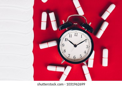 Menstruation. Clock with cotton tampons and sanitary pads on red background. Woman critical days, woman hygiene protection