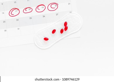 Menstruation cycle concept. Menstruation calendar with sanitary pads, contraceptive pills on white background top view copy space