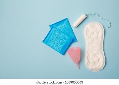 produits de menstruations, hygiène intime, femmes gynécologiques, serviettes hygiéniques, tampons et gobelets de menstruation sur fond bleu