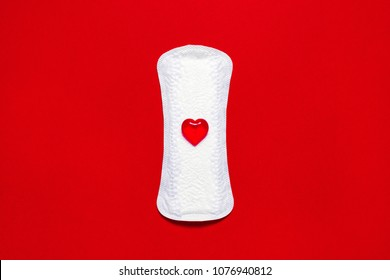 Menstruation. White pad liner with symbol of blood on red background