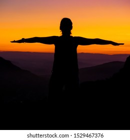 Mental balance. Silhouette of woman with arms in balance on a sunset in the mountains. Orange and Black Silhouette. personal balance. Balance concept and life.