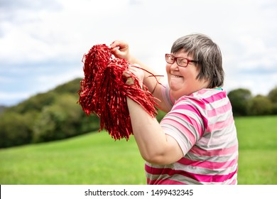 mental disabled woman is cheering with red pompons on a green meadow, having a lot of fun