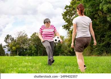 mental disabled woman is playing soccer to train her motor abilities, exercises with a friend or therapist outdoors on a meadow