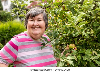 mental disabled woman is showing a apple on a apple tree outdoor in the garden