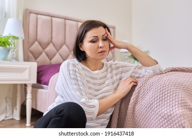 Mental health, age-related physical health problems in middle-aged and mature women. Sad, frustrated, depressed, woman sitting at home on the floor