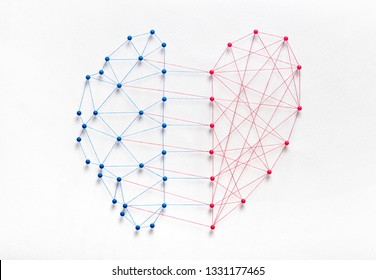 Mental health concept. Network of pins and threads in the shape of half brain and half heart symbolising balance and harmony through emotional intelligence.