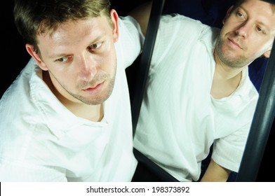 Mental health concept with portrait of a young man reflected in the mirror suggesting mental health problems (bipolar disorder, schizophrenia, multiple personality etc.)
