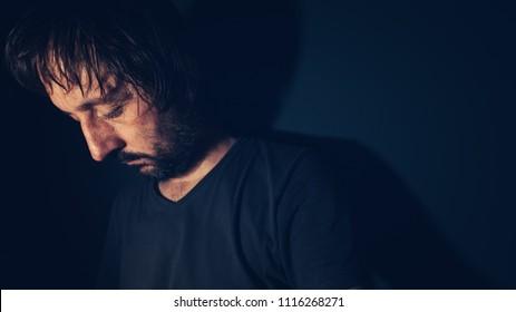 Mental health and depression concept, sad depressed man sulking in dark interior