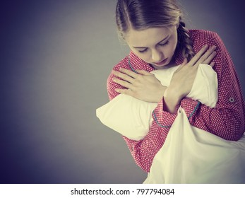 Mental health depression insomia concept. Sad depressive young woman teen blonde girl wearing red pajamas sitting on bed embracing pillow, on grey wall background