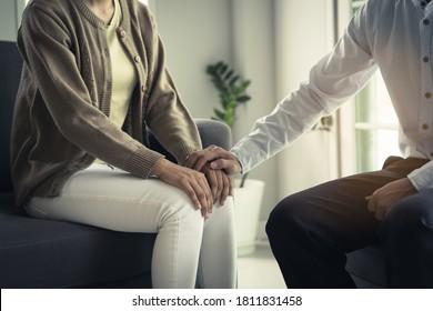 Konzept der psychischen Gesundheit. Stressierter asiatischer Patient, der sich in der Therapiesitzung mit einem Psychologen unterhält, hat ein Gefühl von Empathie und Ärztin, das ihre Hand berührt.