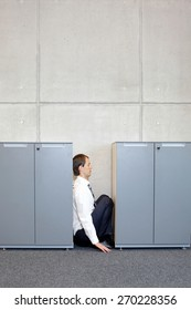 mental health - white sad business man crouching between cabinets