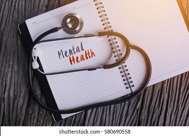 """""""Mental Health"""" Word on Note book With Stethoscope on wooden background."""