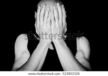 Mental ill depressed and lonely man cover his face with his hands and cry Isolated on black background, depression concept