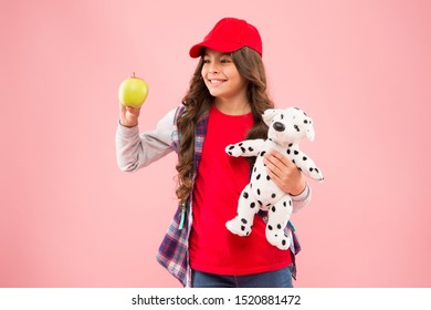 Mental and physical wellbeing. Schoolgirl daily life. Stylish schoolgirl. Girl little fashionable schoolgirl with backpack carry soft toy dog and hold apple. Reduce stress. Healthy lifestyle.