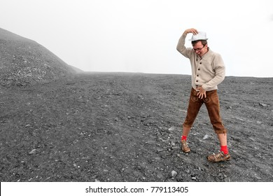 Mentally challenged individual in traditional clothing dances on a moonlike landscape in the mountains of the Swiss alps near Grimentz, Switzerland, on a cloudy day in summer