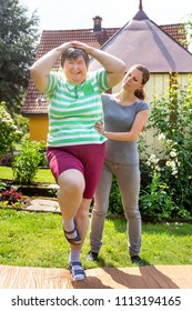 mentally disabled woman is doing some assisted exercises for her fitness