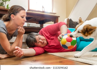 mentally disabled woman is laying on the floor, playing with a trained care dog