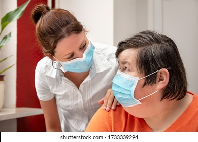 Mentally disabled woman and nurse or caretaker wearing a surgical mask, covid-19 or corona, coronavirus and handicapped people