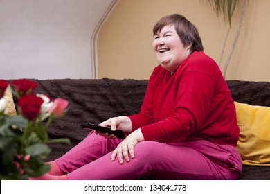 Mentally disabled woman watching television and laughs