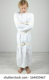 Mentally ill man in strait-jacket on gray background