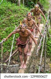 MENTAWAI PEOPLE, SIBERUT ISLAND, INDONESIA – 14 MAY 2017: Men Mentawai tribe crossing the river on a log. 14 May, 2017. Siberut island, Indonesia.