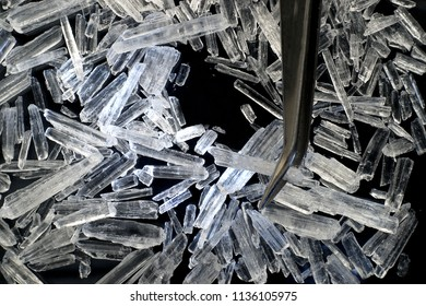 Menthol crystals with tweezers on a black background.