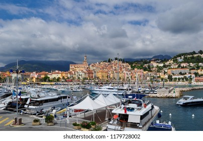 Menton / France — August 8, 2010: a picturesque view of the port of Menton with the old town in the background. Menton is a small town on the Cote d'Azur, or French Riviera, and a popular destination