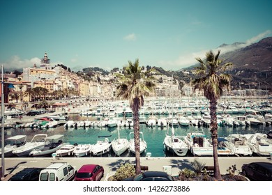 MENTON, FRANCE - JUNE 05, 2019: View of palm tree and harbor with boats in Menton on French Riviera. Provence-Alpes-Cote d'Azur, France.
