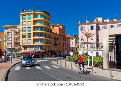 MENTON, FRANCE - MARCH 11, 2017: Urban road along promenade and colorful buildings under blue sky in Menton - small town on Mediterranean coast of French Riviera, popular travel destination.