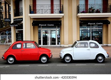 Menton, France - May 14, 2016: Two small Italian cars Fiat 500 Parked in a Parking Lot in Menton. The red car is a Fiat 500 R and the white is a Fiat 500 F