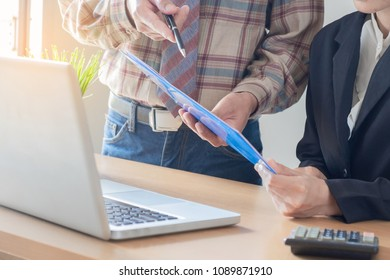 Mentor businessman and businesswoman with graphs in meeting at office desk