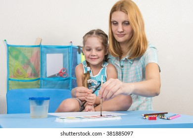Mentor and five year old girl draws paints picture at the table in kindergarten