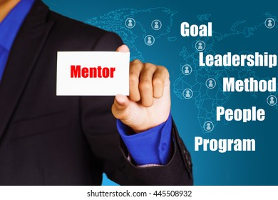 """Mentor"" red text on card hold by confident young business man with word cloud and map on background - business, strategy and finance concept"