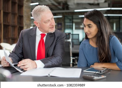 Mentor training young female professional. Middle aged grey haired man in formal suit pointing at notes and instructing young beautiful girl in casual clothes. Business coaching and mentorship concept
