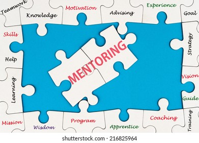 Mentoring concept word cloud on group of jigsaw puzzle pieces