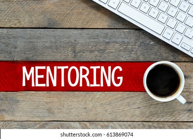 Mentoring / Keyboard and cup of coffee with mentoring inscription on wooden background