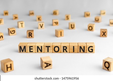 Mentoring - word from wooden blocks with letters, help and advice mentoring concept, random letters around, white  background
